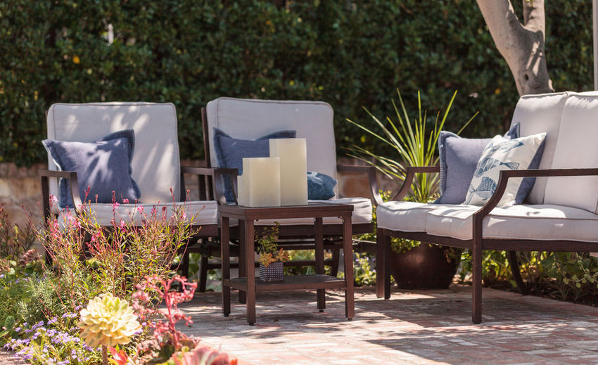 Patio furniture and feng shui garden decor located in a private small patio with plants and flowers Archival Candles Chair Chairs Couch Day Flower Garden Horizontal No People Outdoors Patio Patio Furniture Pillows Summer Table Tranquility