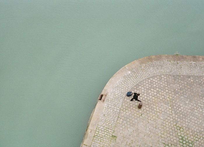 High angle view of man walking on pier by sea