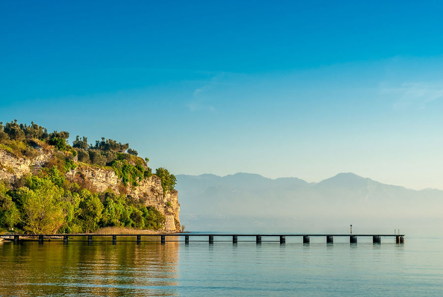Pier at Lido delle bionde. Sirmone, Italy. Alps Blue Calm Water Clear Sky Day Garda Italian Jetty Lake Lido Mountain Nature No People Outdoors Peninsula Pier Quiet Reflections Scenics Sirmione Tranquil Scene Tranquility Warm Water