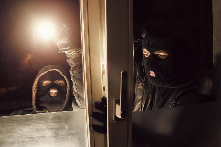 Burglars With Illuminated Flashlight Looking Through Door
