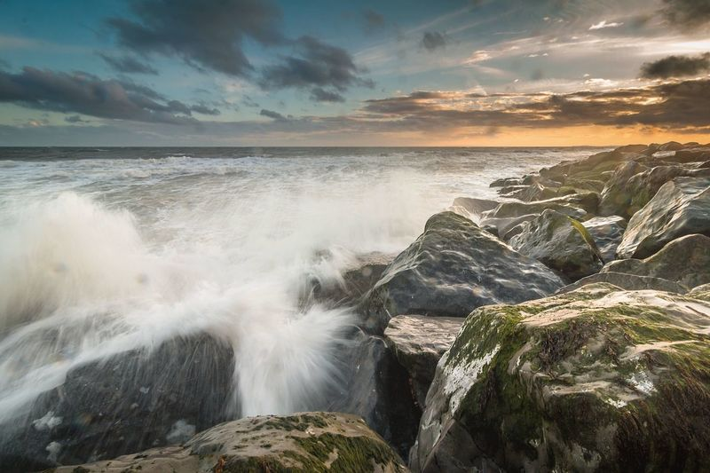 Waves splashing on rocks in sea during sunset