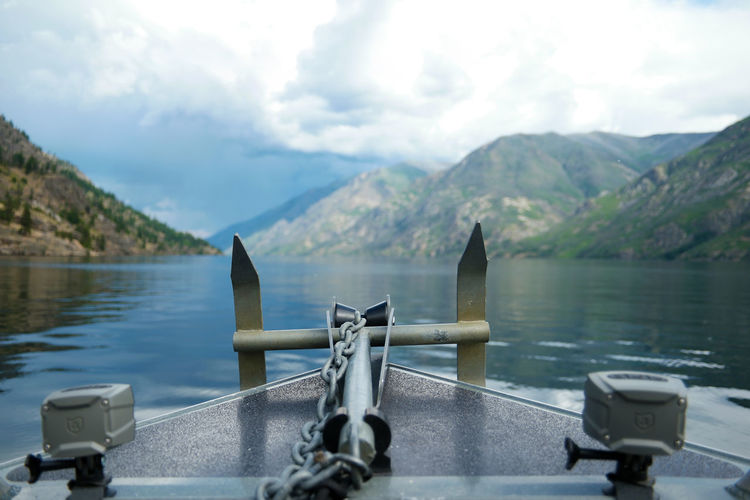 Scenic view of boat anchor against lake and mountains