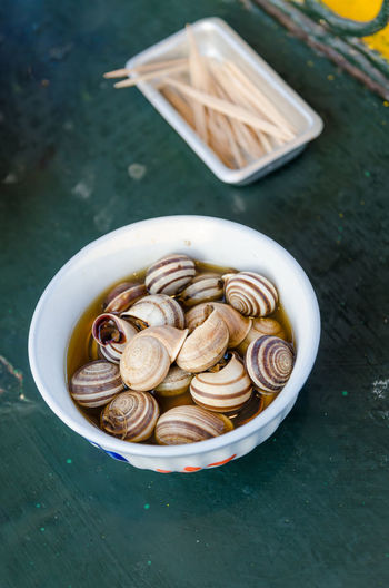 High angle view of boiled snails in bowl on table