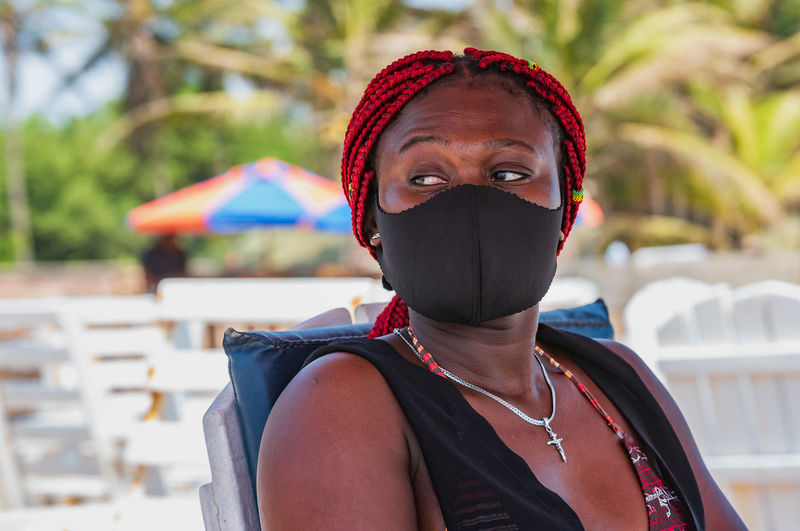 African woman sitting on a beach with black mouth mask in labadi accra ghana west africa