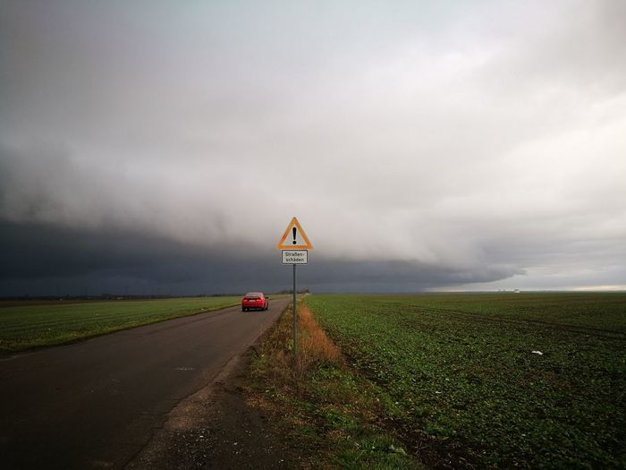 Storm Cloud Storm Rain Cloud - Sky Landscape Rural Scene Thunderstorm Nature Beauty In Nature Scenics Grass Field Fieldscape Fields Road Road Sign Road To Nowhere Car Street Sign Warning Sign Roadway Roadway Damage Wasteland Tristesse Wintertime