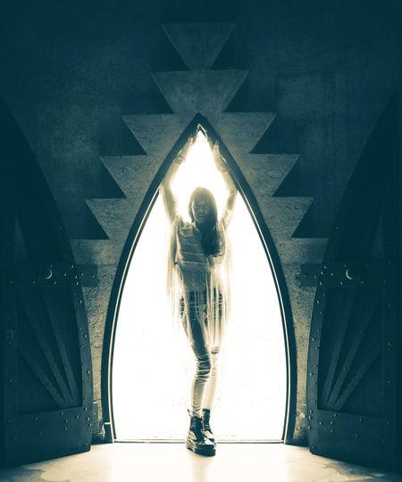 Woman walking in illuminated tunnel