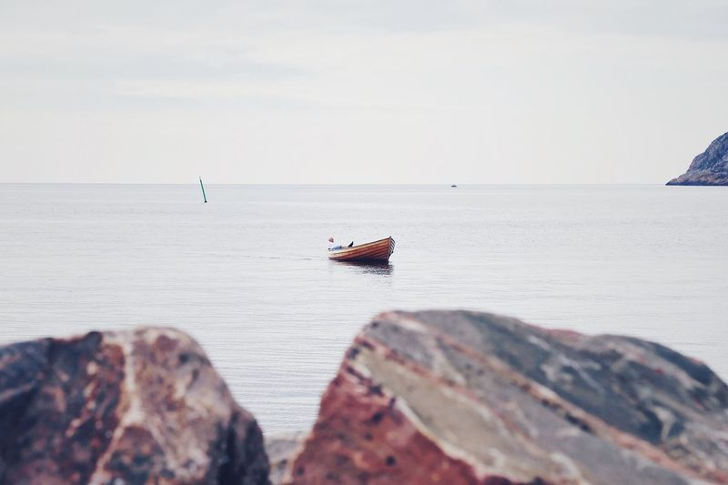 Lonely man in a small wooden boat Calm Sea Rocks Stones Coast Line  Horizon Over Water Tranquility Tranquil Scene Sitting Down Coastal Landscape Coastline Landscape Water Sea Coast Sea Water Nautical Vessel Sky Horizon Over Water Horizon Beauty In Nature Rock Mode Of Transportation Transportation Land Tranquility Nature Day Scenics - Nature Idyllic Tranquil Scene