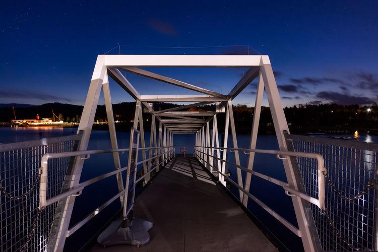 Metallic pier over river at night