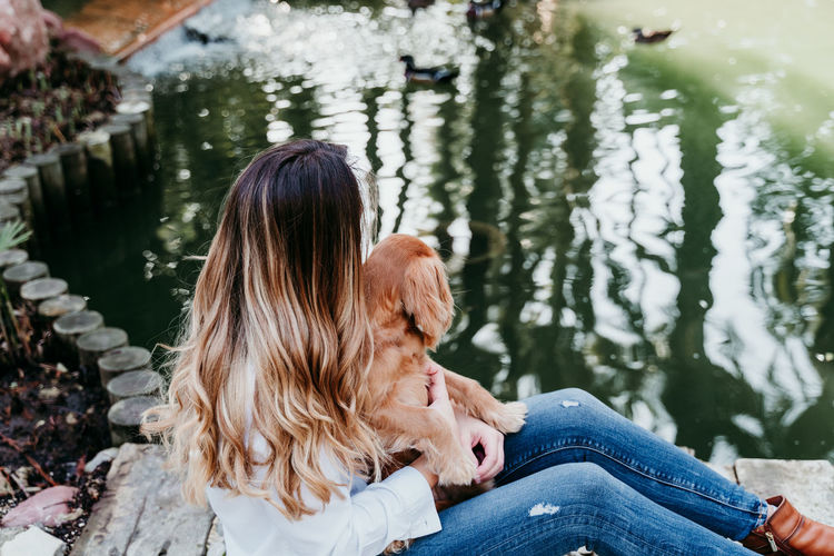 Dog with woman by pond at park