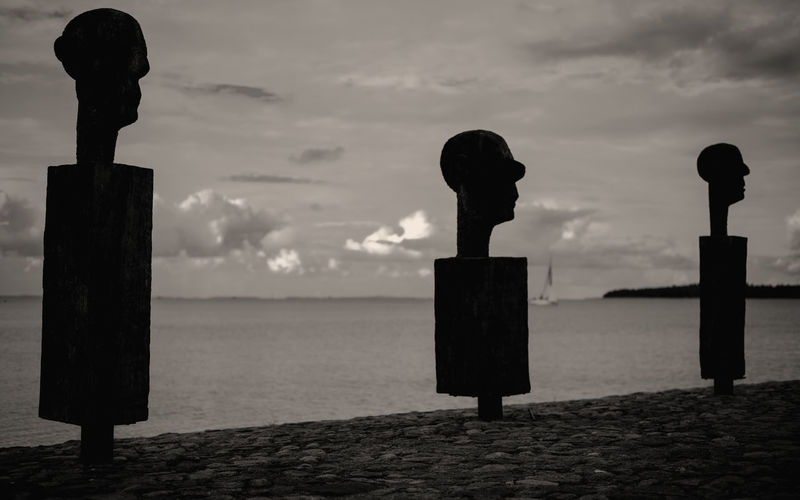 Silhouette sculpture on wooden post by sea against sky