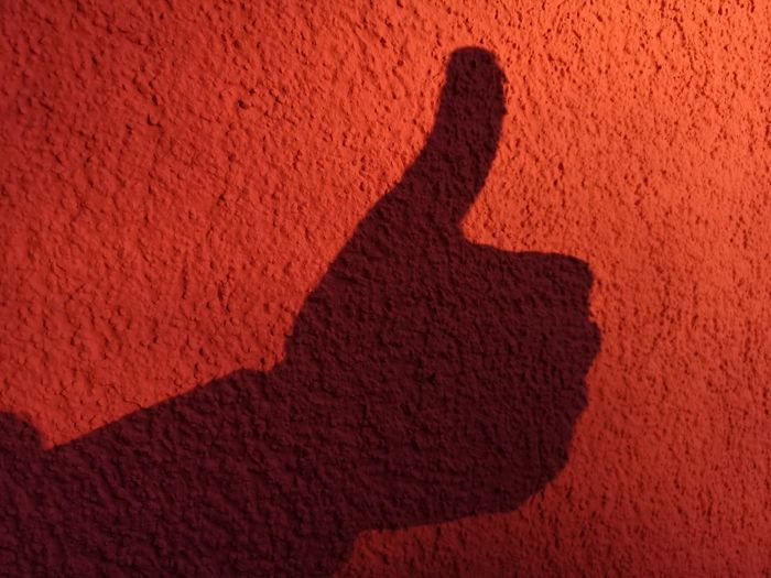 Shadow of thumbs up against a reddish background of a roughly rubbed plaster. Roughly Round Rubbish Plaster Soft Light Reddish Background Thumbs Up Against Shadow Red Silhouette Sand Sunlight Close-up Thumb Human Finger Hand Sign Focus On Shadow Textured  Rough