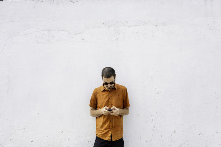 Man using smart phone standing against wall