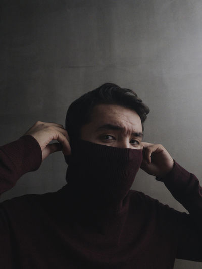 Portrait of young man holding covering face against wall