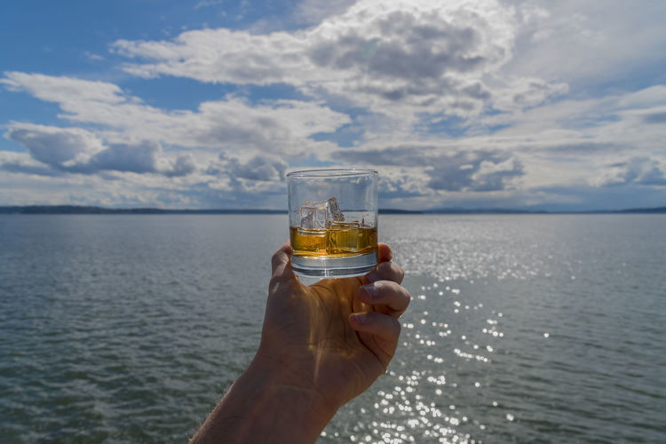 Cropped hand of person holding whisky glass against sea and cloudy sky