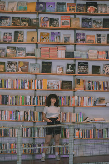 Publication Shelf Book Bookshelf Indoors  One Person Large Group Of Objects Library Lifestyles Women Front View Arrangement Education Choice Abundance Leisure Activity Portrait Collection Looking At Camera Order Hairstyle