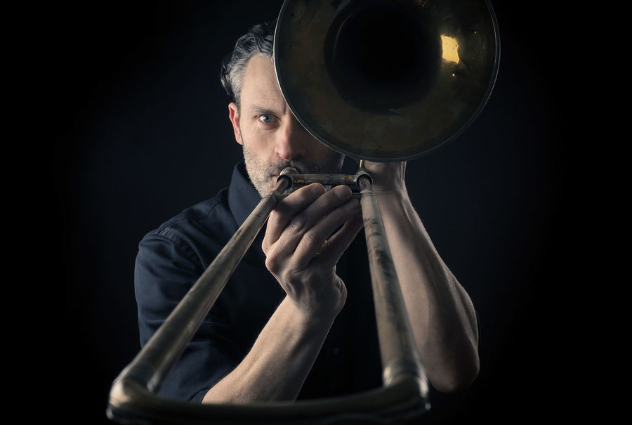 Musician with trombone Adult Adults Only Black Background Classical Music Close-up Front View Holding Indoors  Jazz Music Mature Adult Mature Men Music Musical Instrument Musician One Man Only One Person People Performance Playing Real People Studio Shot Trombone Wind Instrument