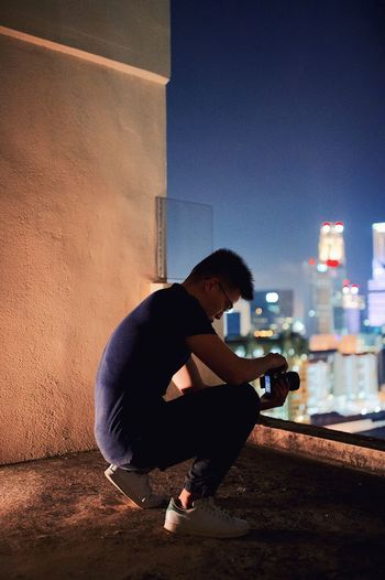 Young man crouching on building terrace at night