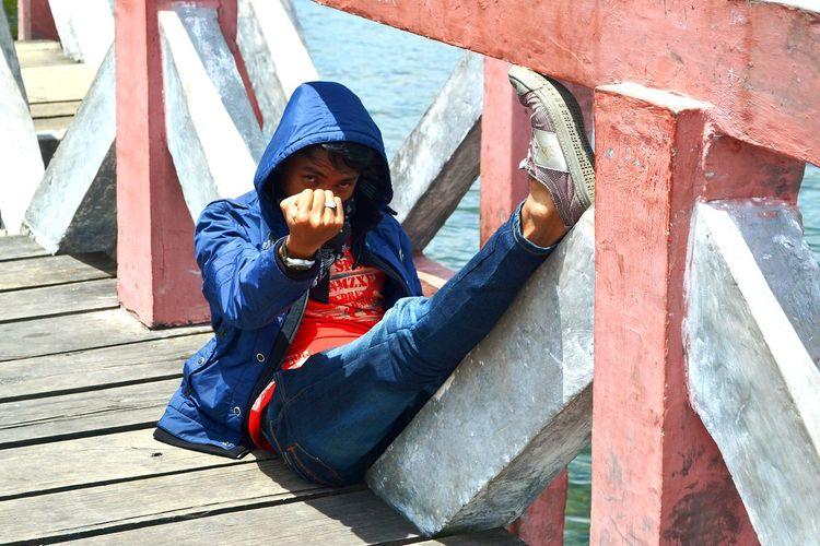 Full length of man sitting on pier