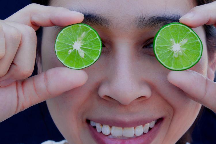 Close-up portrait of woman holding lemon slices