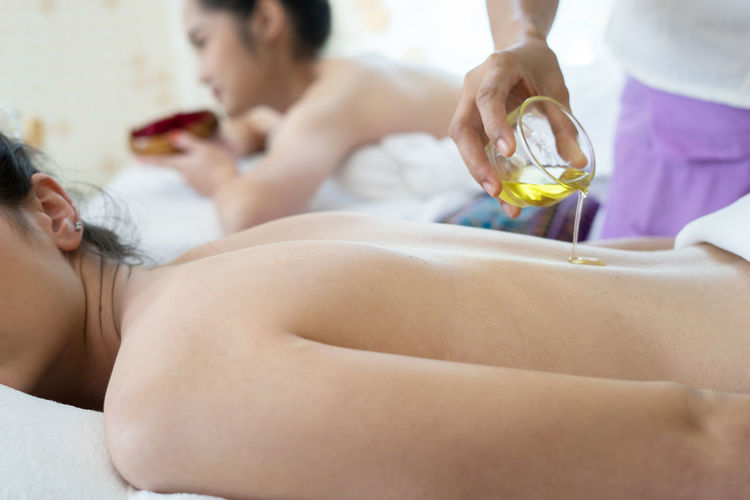Massage therapist putting oil on back of woman in spa