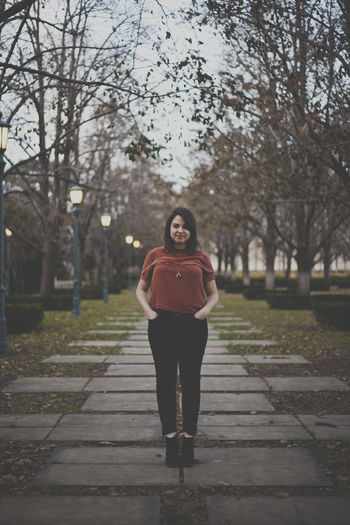 Portrait of beautiful woman standing on footpath at park