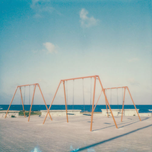 Empty swings hanging on promenade against sea and sky