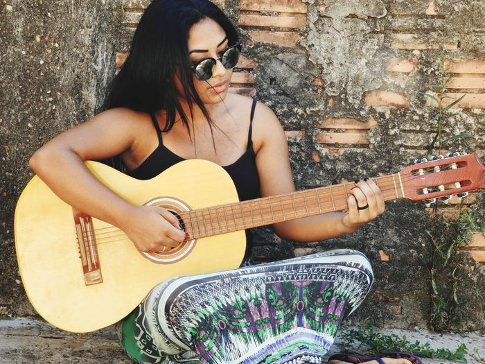 Young woman playing guitar while sitting by old wall