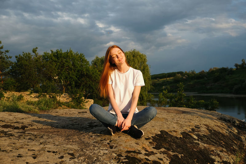 Portrait of smiling woman sitting against sky