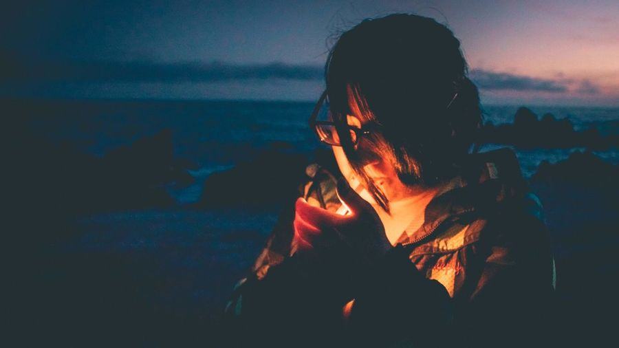 Close-up of woman igniting cigarette at beach during sunset
