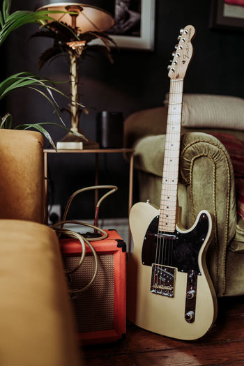Acoustic Guitar Arts Culture And Entertainment Close-up Domestic Room Electric Guitar Focus On Foreground Furniture Guitar Home Interior Indoors  Music Musical Equipment Musical Instrument Musical Instrument String No People Shoe Sofa Still Life String String Instrument