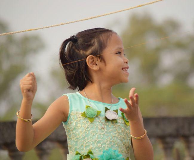 Smiling girl flying kite outdoors