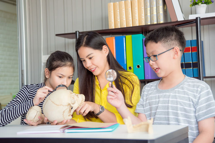 Teacher Asian  Student School Child Education Kid Girl Classroom Kids Learning People Female Helping Class Montessori ASIA Woman Mother Children Portrait Study Home Students Together person Elementary Childhood Pupil Room Teaching Happy Table Library Young Adult Cute Thai Science Biology Boy