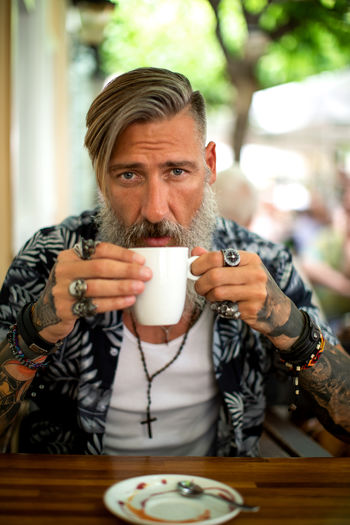 Attractive hipster with a beard is drinking coffee in a coffee shop Portrait One Person Lifestyles Coffee - Drink Coffee Cup Coffe Shop Hipster Beard Bearded Tattoo Modern Smart Phone Jewelry Attractive Drinking Outdoors Relaxing Shirt Looking At Camera Enjoyment Tourist Biker Rocker Sitting Tree