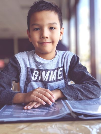 Portrait of smiling boy with menu on table sitting in restaurant