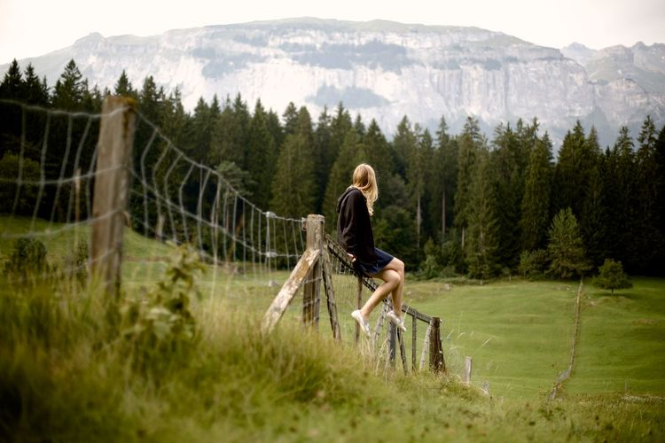 Full Length Of Woman Sitting On Fence Over Field