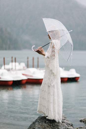 Man with umbrella standing on lake during rainy season