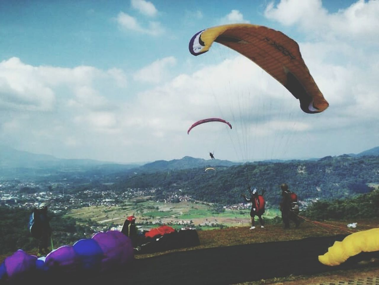 parachute, paragliding, extreme sports, real people, adventure, leisure activity, sky, lifestyles, mid-air, gliding, outdoors, flying, men, one person, day, mountain, landscape, cloud - sky, sport, nature, skydiving, full length, beauty in nature, people