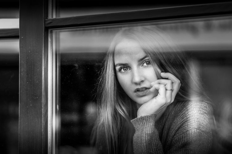 Portrait of a beautiful young woman looking through window