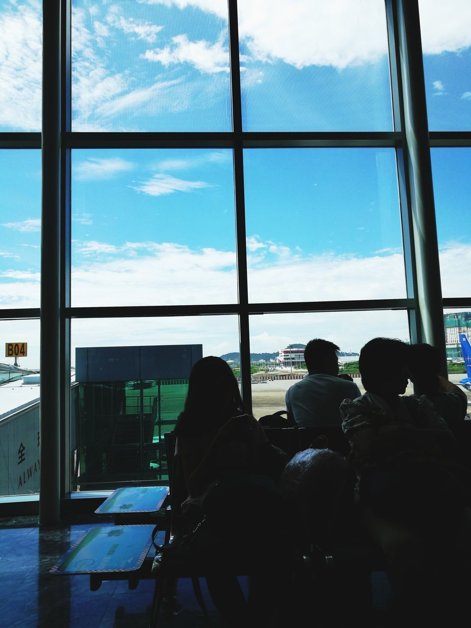 window, transparent, real people, glass - material, men, indoors, sky, sitting, group of people, people, public transportation, day, lifestyles, airport, travel, cloud - sky, transportation, mode of transportation, seat, airport departure area, waiting