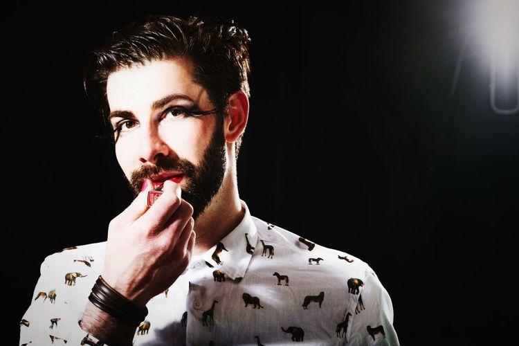 Portrait of man applying lipstick standing against black background