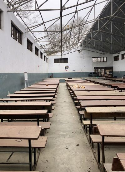Empty chairs and tables against building