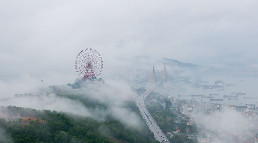 Aerial view of ferris wheel in city during foggy weather
