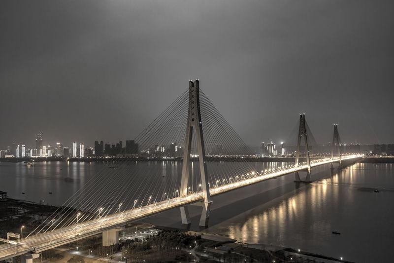 Bridge over river in city at night