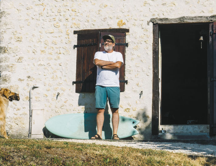portrait of mature surfer man in front of his old house Vacations France Surfing Surfboard House Mature Adult Man Grey Bearded Surfer Morning Retirement Retired Paradies Dream Outdoors Architecture Building Exterior Full Length One Person Front View Looking At Camera Portrait Casual Clothing Real People Standing Leisure Activity Young Adult Lifestyles Young Men Day Built Structure Men Nature Shorts