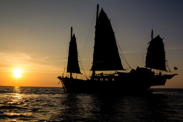 Old junk style sailboat sailing into the sunset of the Andaman Sea in Thailand Junk Silhouette Beauty In Nature Horizon Over Water Mode Of Transportation Nature Nautical Vessel No People Outdoors Reflection Sailboat Sailing Scenics - Nature Sea Ship Silhouette Sky Sunlight Sunset Tranquil Scene Transportation Travel Vessel Water Waterfront