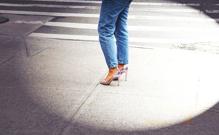 Low section of woman standing on footpath