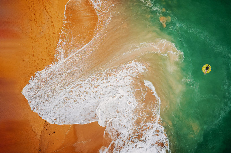 Aerial view of woman swimming on the yellow swim ring in the turquoise sea. Beach on aerial drone top view with ocean waves reaching shore. Top view from drone Water Sea Motion Surfing Wave Aquatic Sport Beach Land Sport Nature Outdoors Beauty In Nature Scenics - Nature Drone  Relax Summer Sand Holiday Aerial Seascape Mediterranean  Tropical Vacations