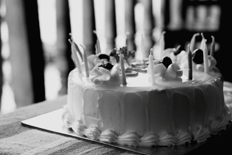 Close-up of birthday cake with candles on table