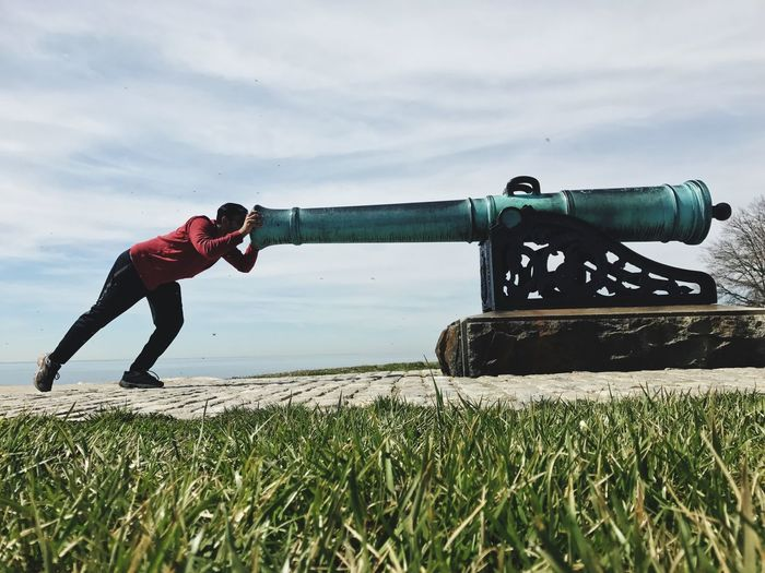 Man Pushing Cannon Against Sky