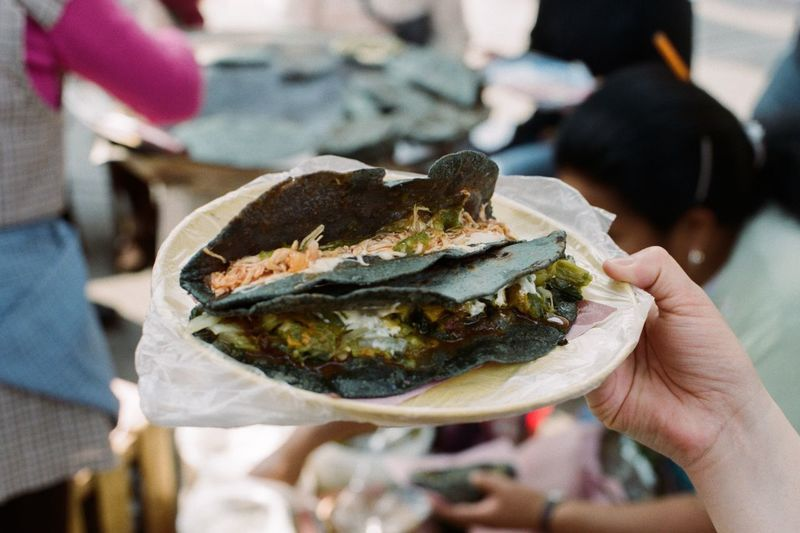 Cropped Image Of Woman Holding Plate With Blue Corn Quesadillas